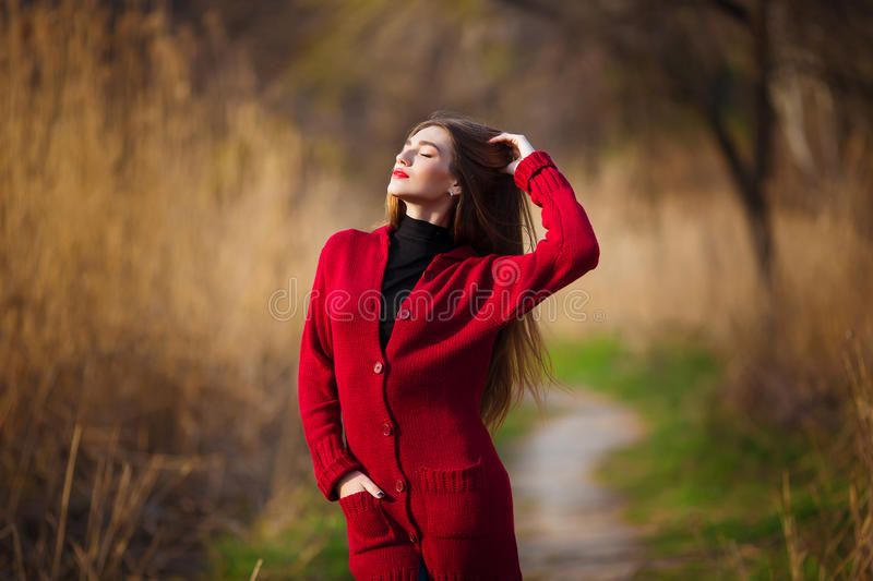 Dreaming young woman. Beautiful female with long healthy hair enjoying nature in park wearing red cardigan. Spring stock photography