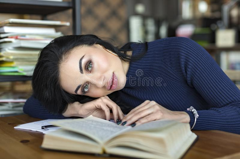 Dreaming young woman with book at table in cafe stock images