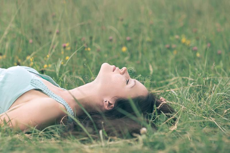 Dreaming young woman relaxing on a hot summer day stock image