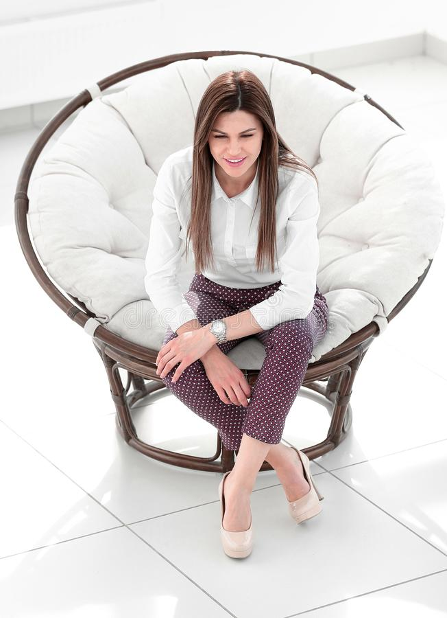 Dreaming young woman sitting in a soft round chair stock images
