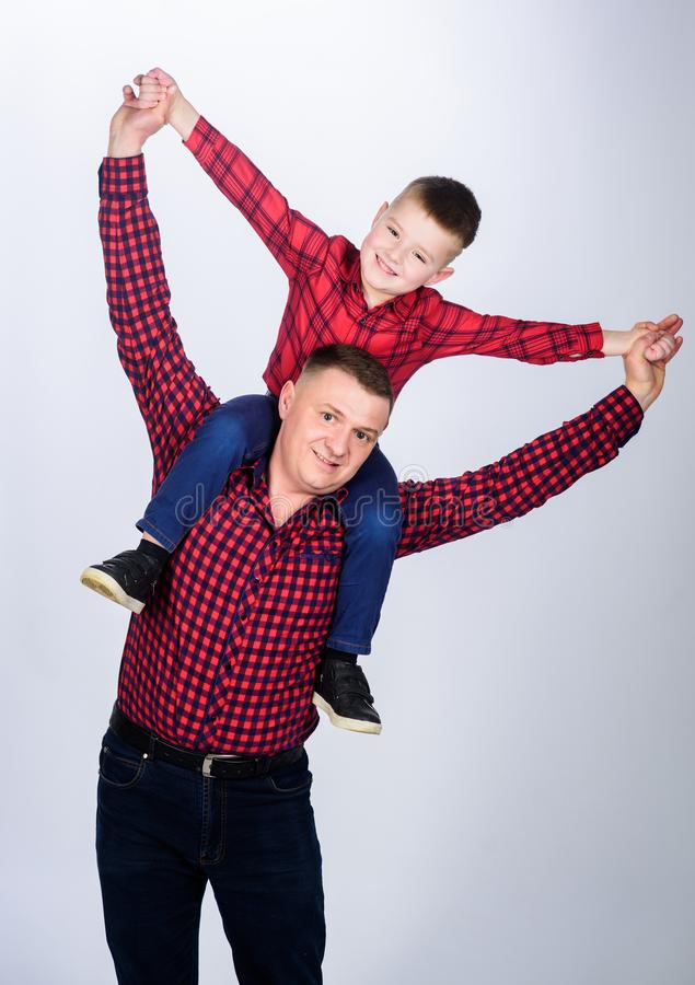 In the dreamland. happy family. little boy with dad man. fathers day. childhood. parenting. father and son in red. Checkered shirt. Cowboy couture. No cares and stock photos
