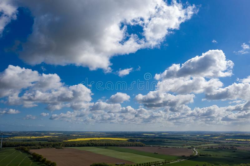 Dreamlike blue sky with white sheep clouds over green and yellow fields. A dreamlike blue sky with white sheep clouds over green and yellow fields royalty free stock photos
