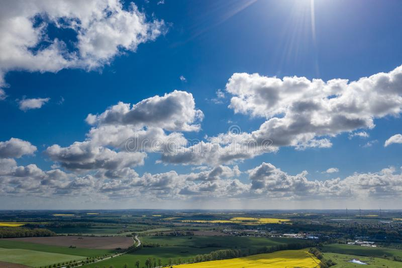 Dreamlike blue sky with white sheep clouds over green and yellow fields. A dreamlike blue sky with white sheep clouds over green and yellow fields royalty free stock images