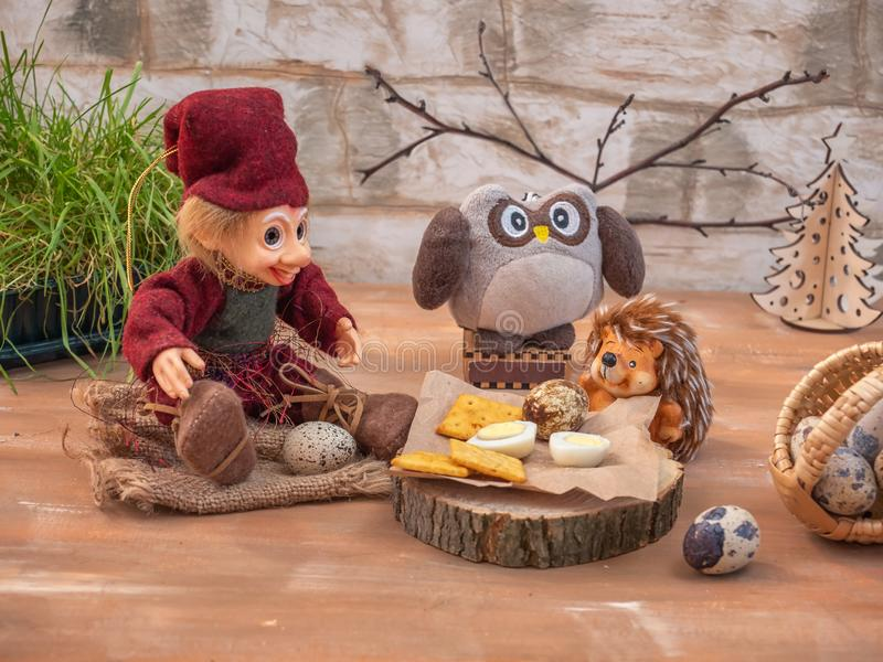 Dreamlike card with toy characters. Three friends Lesovik, an owl and a hedgehog settled down with a lunch of eggs and cracker. Biscuits on forest hemp. Near a stock images