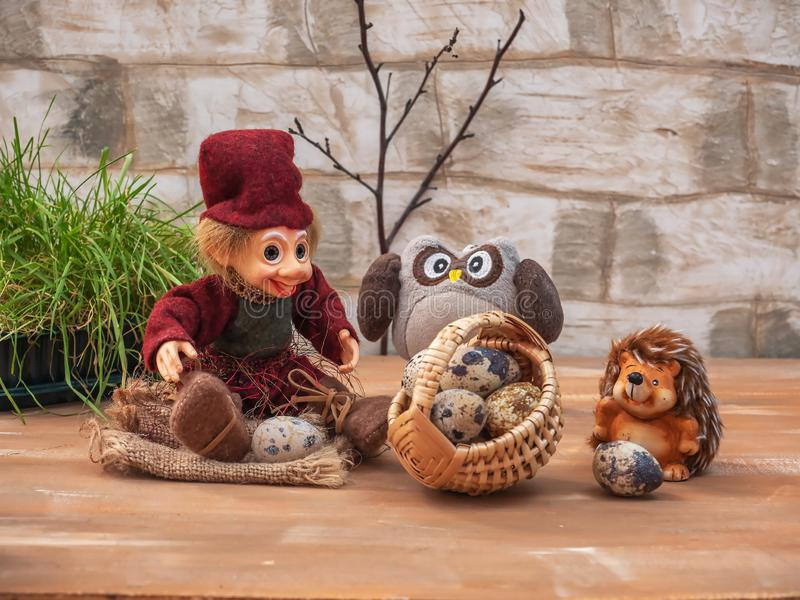 Dreamlike card with toy characters. Three friends are resting on a forest clearing. They carry a large basket of quail eggs. Dreamlike card with toy characters royalty free stock photography