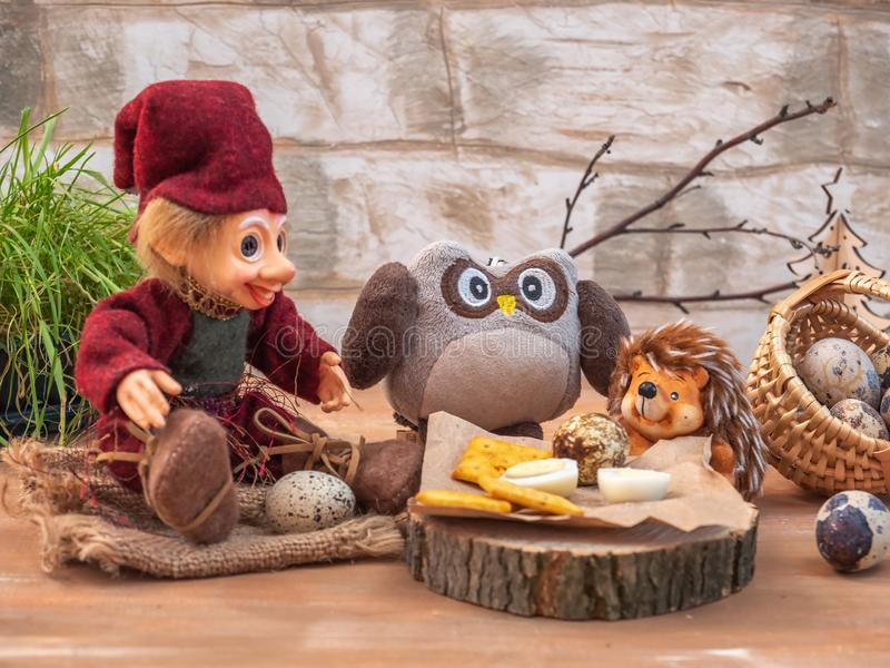 Dreamlike card with toy characters. Three friends Woodman, an owl and a hedgehog dine, they eat eggs and cracker cookies on the. Dreamlike card with toy royalty free stock photos