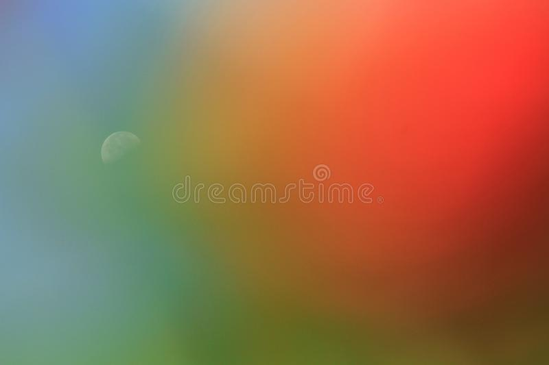 Dreamlike moon in blue sky. In the morning in summer on pink foreground royalty free stock photo