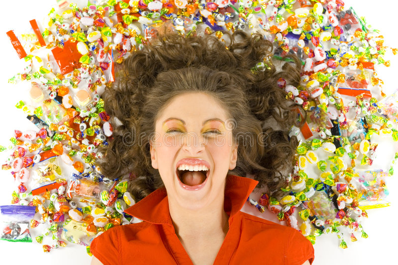 Dreams come true. Young, beautiful woman lying on floor among candys with closed eyes. Laughing, front view. White background royalty free stock photo