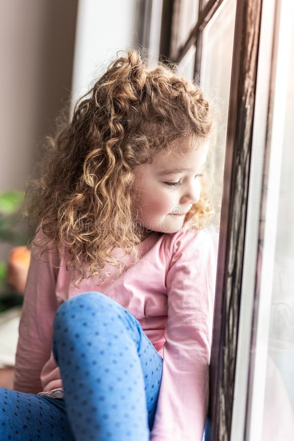 Portrait of cute little female that enjoying the moment. Dreams come true. Beautiful girl expressing positivity while looking through the window royalty free stock image