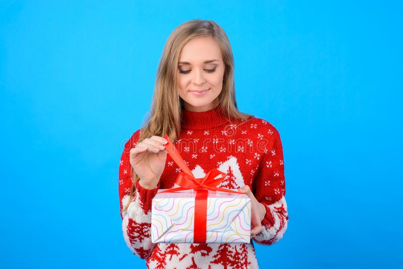 Dreams come true on Christmas! It`s magic time! Cute pretty girl. In nice pullover is unpacking a box she received from her beloved person. Copy-space, she is royalty free stock photo