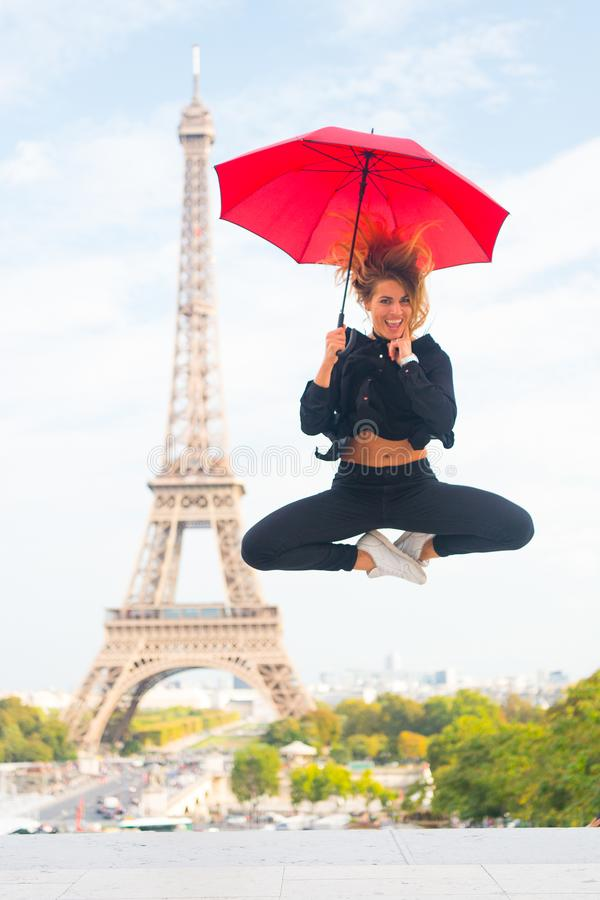 Dreams come true concept. Lady tourist sporty and active in Paris city center jumps up. Girl tourist enjoy walk and royalty free stock image
