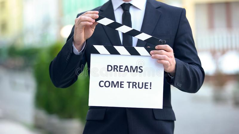 Dreams come true phrase on clapperboard in hands of producer, cinematography. Stock photo royalty free stock photos