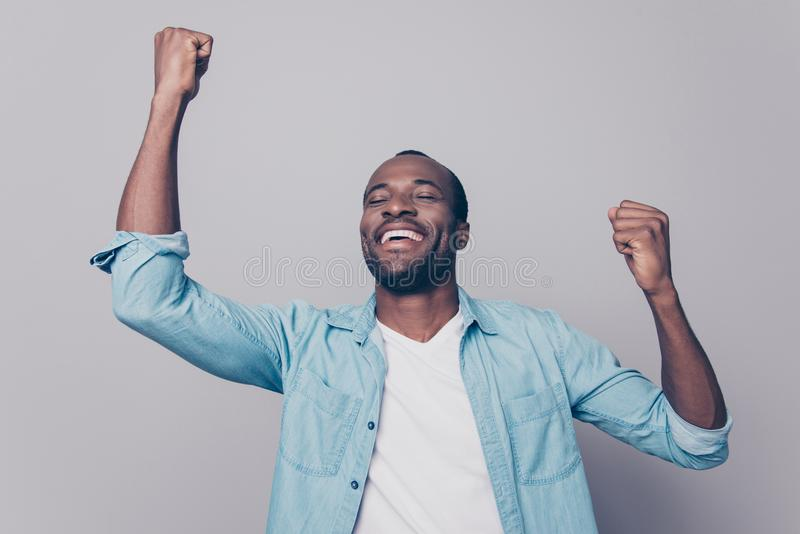 Dreams come true! Portrait of excited cheerful handsome delightful joyous wearing casual denim shirt guy raising his hands up, is. Olated on grey background royalty free stock photo
