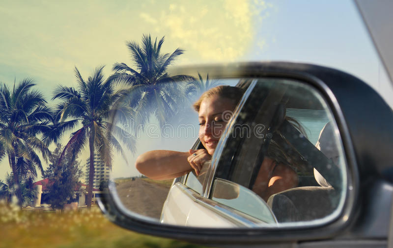 Dreams of exotic travel. Photo of the young girl in a mirror of the car which dreams of exotic travel royalty free stock photos