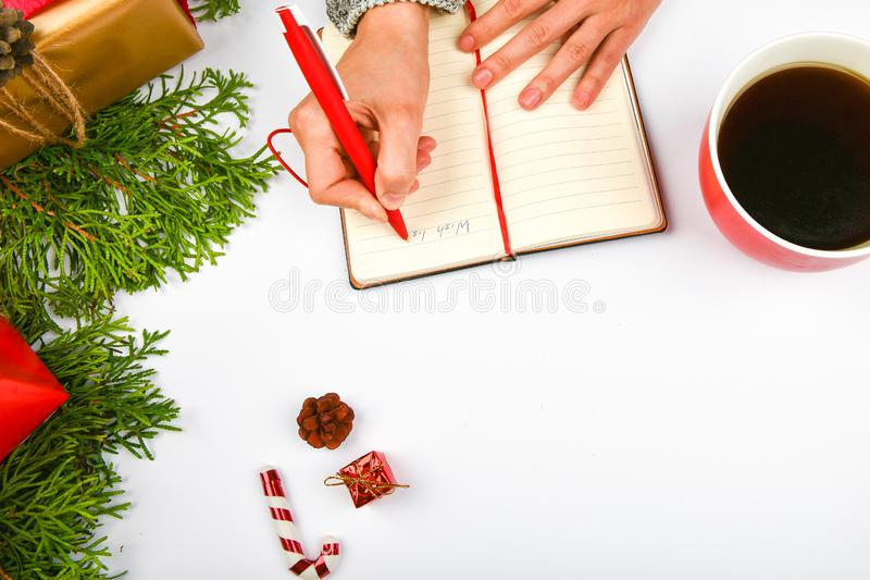 Dreams of goal plans make a list for writing a New Year`s Christmas concept in a notebook. Woman hand on the background of fir royalty free stock images