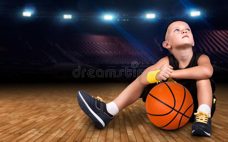 Boy basketball player with a ball sitting on the floor in the gym and dreams of great victories. stock photography