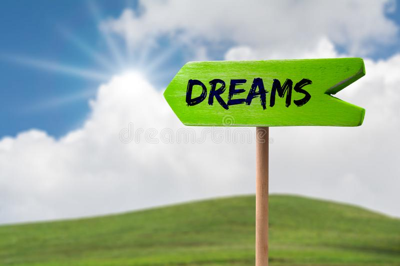 Dreams arrow sign. Dreams green wooden arrow sign on green land with clouds and sunshine royalty free stock images