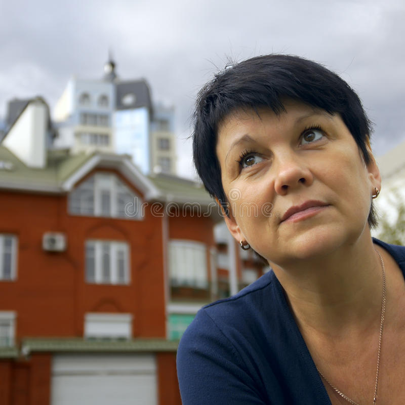 Dreams of home. A woman on a background of cottages stock image