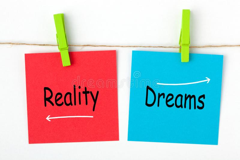 Dreams and Reality. Dreams versus Reality words written on color notes with wooden pinch. Business concept royalty free stock photos