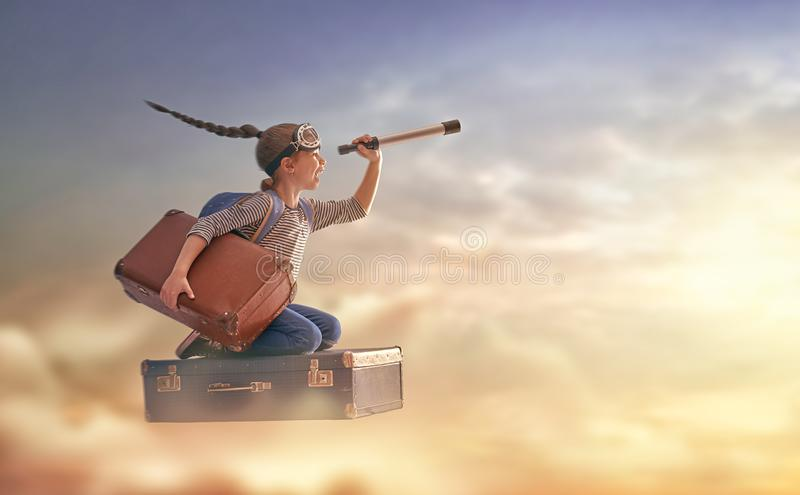 Dreams of travel. ! Child flying on a suitcase against the backdrop of sunset stock images