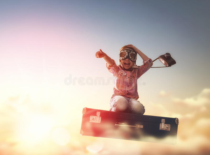 Dreams of travel. ! Child flying on a suitcase against the backdrop of a sunset royalty free stock photography