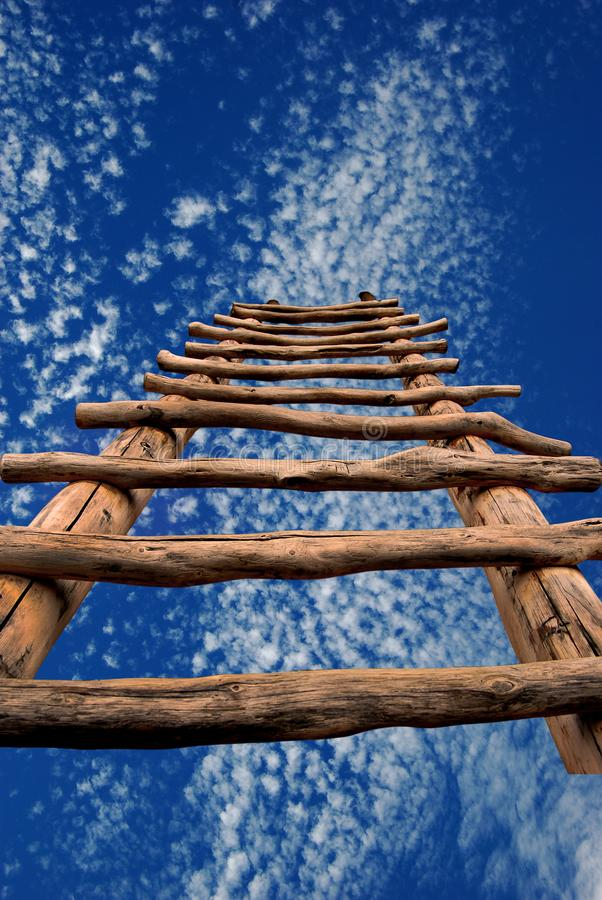Dreamscape with Kiva Ladder and Sky. Conceptual image of a traditional kiva ladder ascending into a blue sky with white clouds stock photography