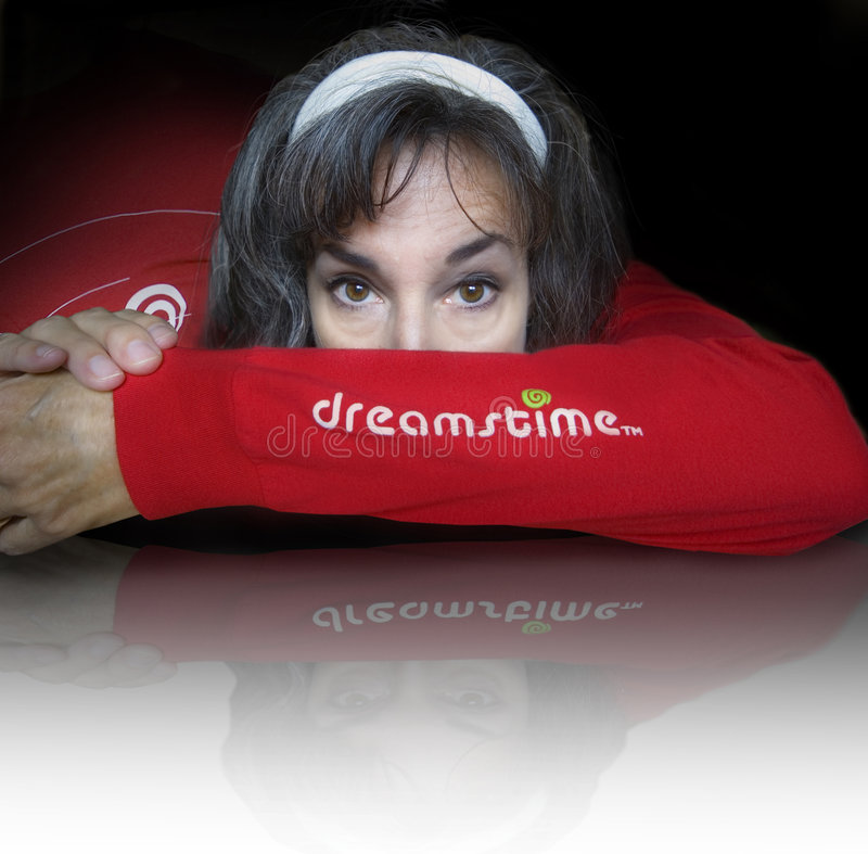 Dreamstime logo. A woman's head is tucked into the elbow of a red Dreamstime shirt