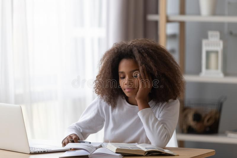 Dreamy black teenager distracted from preparing homework royalty free stock photography