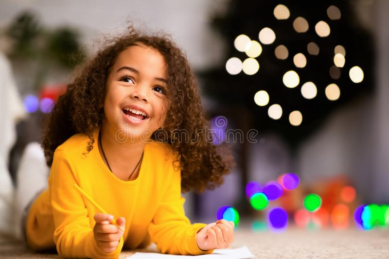 Dreamy african child writing wishlist for Christmas holidays royalty free stock images