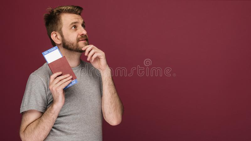 Dreamy bearded man in a t-shirt holding air tickets and passport stock photos