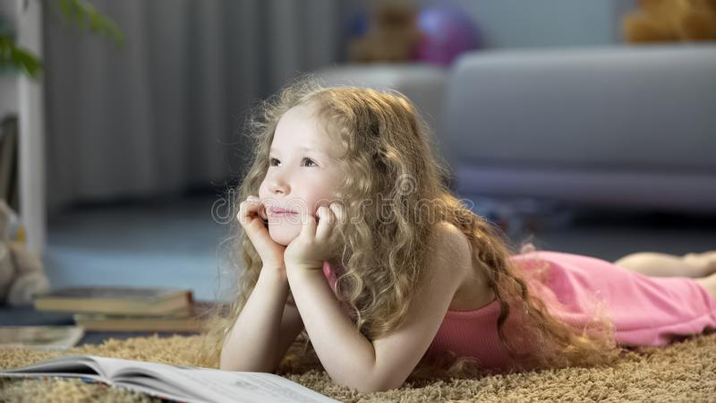Dreamy cute girl lying on floor in cozy room at home, happy child thinking stock photos