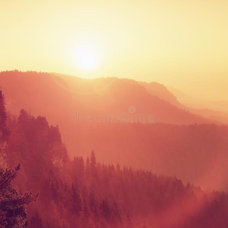 Dreamy dayreak in landscape, spring orange pink misty sunrise in a beautiful valley of rocky mountains park. Dark sharp hills increased from gentle fog royalty free stock photography