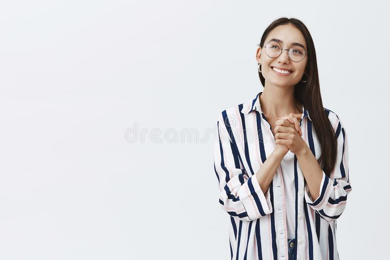 Dreamy feminine girlfriend in trendy glasses and striped blouse looking with delight and admiration at upper left corner. Clasping hands over chest while royalty free stock image