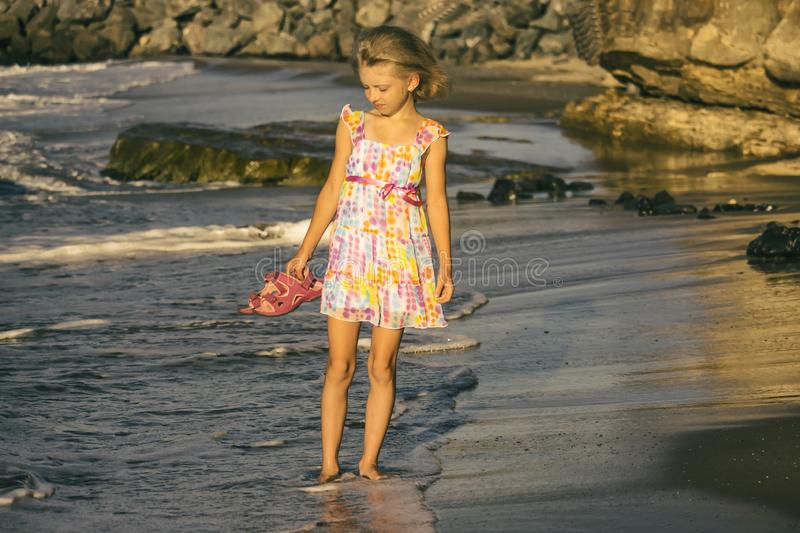 A dreamy girl blonde in a beautiful dress walks along the shore, soft focus royalty free stock images