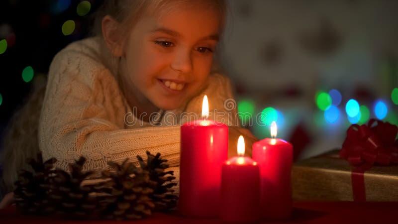 Dreamy girl enjoying view at burning candles, waiting for X-mas celebration royalty free stock photo