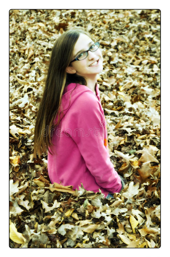Dreamy Girl in Fall Leaves. A beautiful young teen sitting in colorful leaves of autumn with a smile and dreamy expression. Concept of changing seasons or from royalty free stock photos