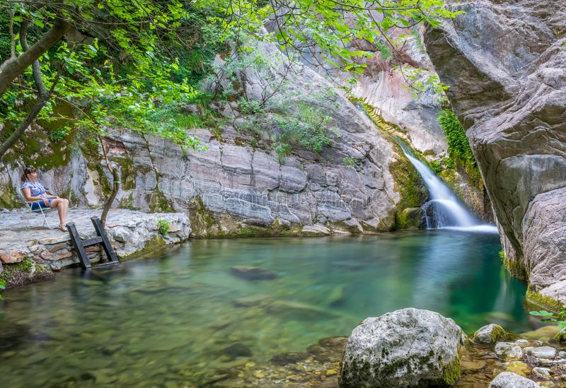 A dreamy girl is meditating in a lagoon near a waterfall. royalty free stock photo