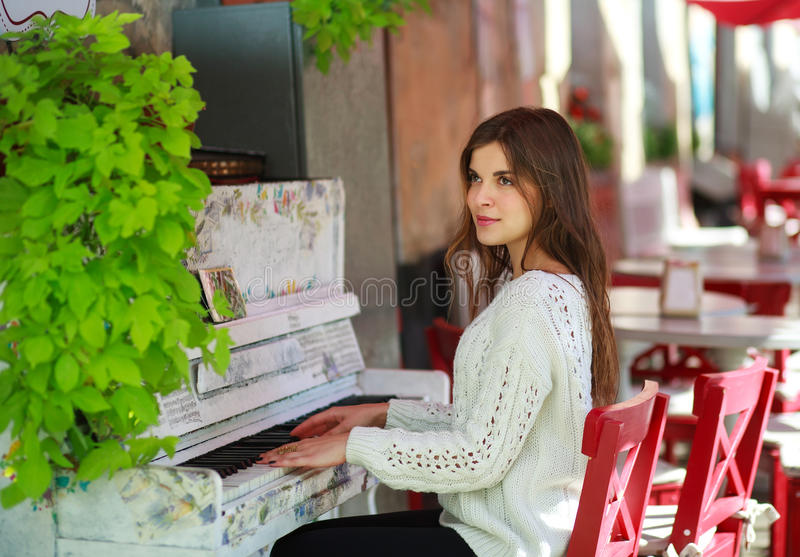 Dreamy girl playing on an old piano in cafe royalty free stock image