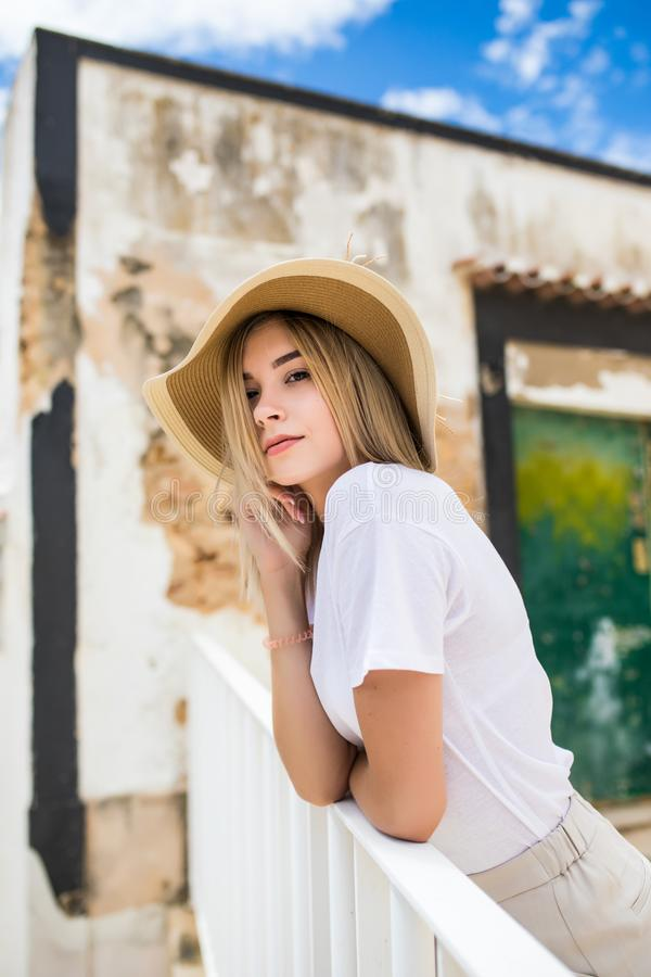 Dreamy girl sitting on terrace in straw hat and sunglasses. Outdoor portrait of elegant woman relaxing. Dreamy girl sitting on terrace in straw hat and stock photo