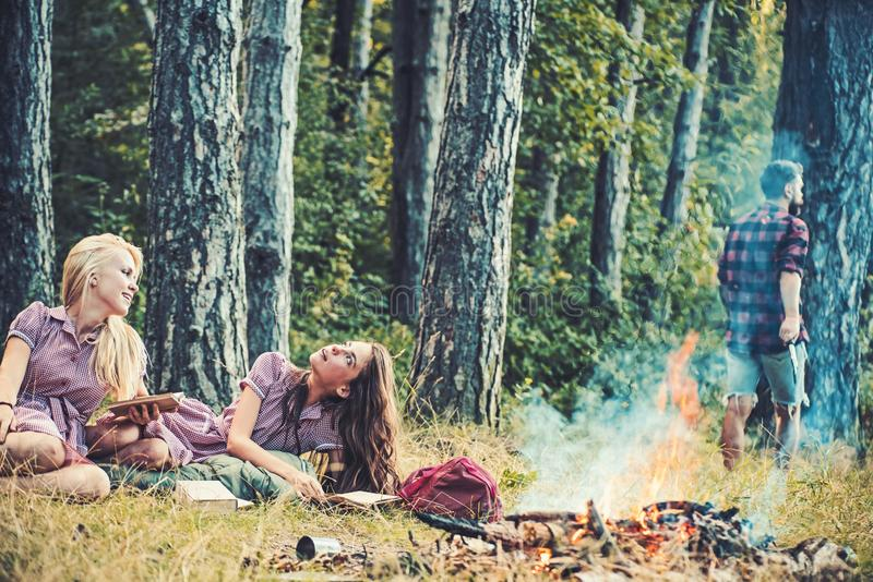 Dreamy girls reading books by campfire. Women lying on grass. Guy walking into woods stock images