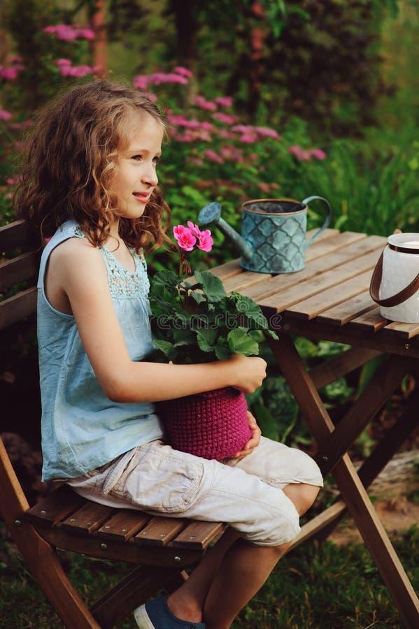 Free Dreamy Happy Child Girl Relaxing In Summer Evening Garden With Heranium Flower In Pot Stock Photos - 116280863