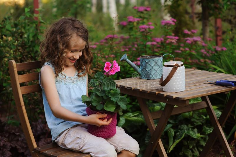Dreamy happy child girl relaxing in summer evening garden with heranium flower in pot. Teaching kids to love nature and take care about plants royalty free stock photos