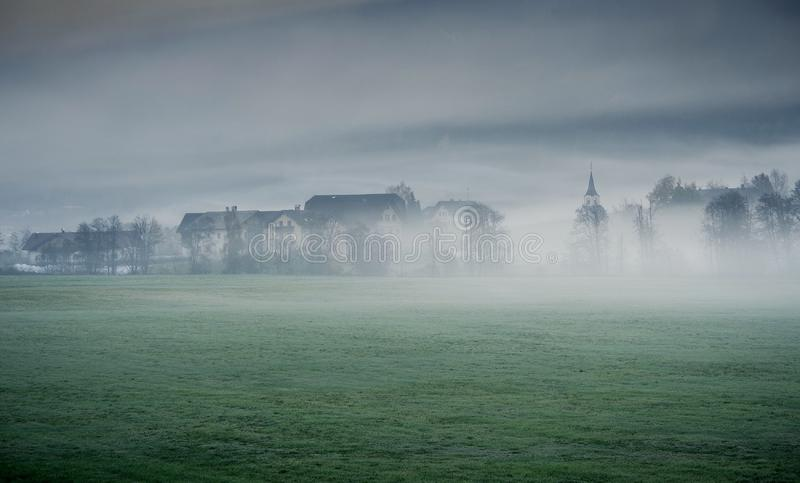 Dreamy landscape lost in thick fog, Valle di Casies. stock images