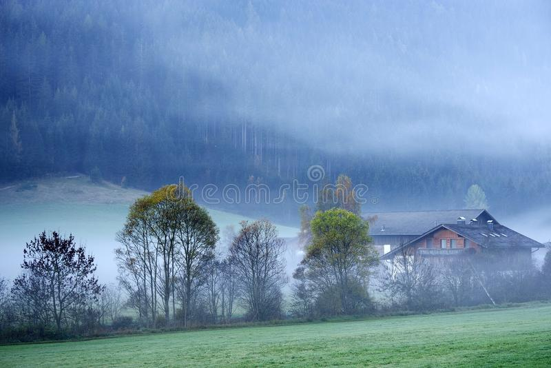 Dreamy landscape lost in thick fog, Valle di Casies. stock photography