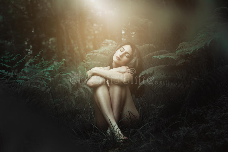 Dreamy light over forest nymph. Mystical forest nymph surrounded by dreamy light. Fantasy and surreal stock photo
