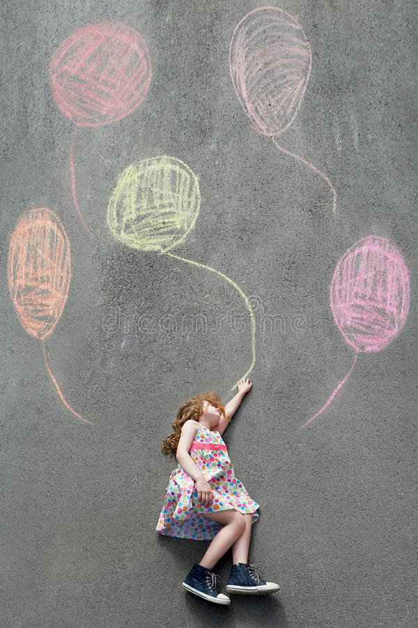 Dreamy little girl lying on the pavement with painted balloons. royalty free stock photos