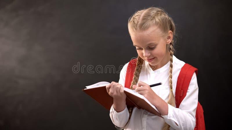 Dreamy little schoolgirl writing in notebook, doing homework against blackboard stock photography