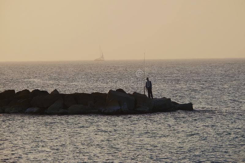 Dreamy man looking at the boat during sunset. А lone fisherman on a rocky shore staring at the sea. Dreamy man looking at the boat during sunset. A little man stock photography