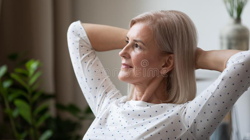 Dreamy mature woman relaxing leaning back, thinking about future. Dreamy mature woman relaxing leaning back close up, thinking about good future alone at home royalty free stock photography