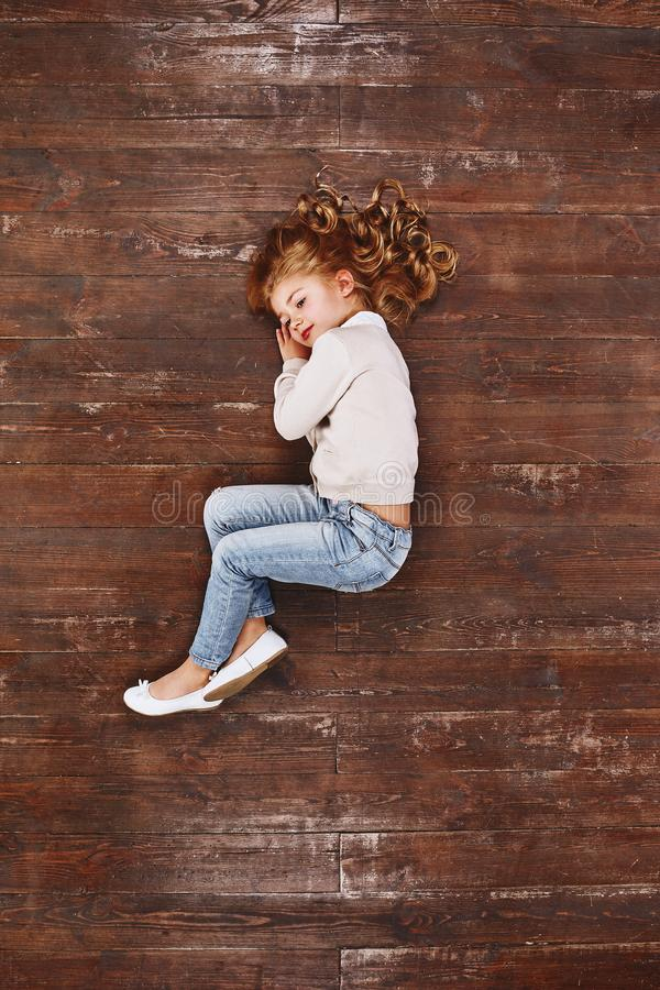 Dreamy mood. Girl curling up, lying on the floor, looking away and smiling royalty free stock photo